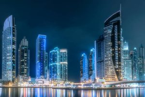 Modern buildings of Dubai Marina bay with lights at night on background, view from Palm Jumeirah, UAE